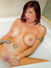 Curvaceous red head teases her wet pussy with the shower head