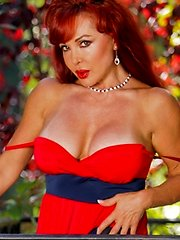 Classy red haired Anilos pin up exposes her cleavage outside
