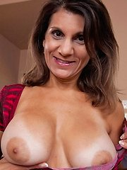 Mature lady shows us her huge tan line accented titties